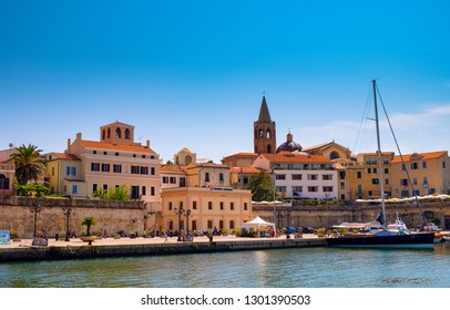Alghero, Sardinia / Italy - 2018/08/10: Summer view of the Alghero historic old town quarter at the Gulf of Alghero at Mediterranean Sea