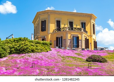 Alghero, Sardinia, Italy - April 25, 2016: Picturesque view of building of Villa Mosca Hotel in Alghero old town. Hill covered with Saponaria flowering plants on the foreground. Mediterranean seacoast