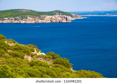Alghero, Sardinia, Italy - Panoramic view of the Gulf of Alghero with cliffs of Punta del Giglio and city of Alghero in background
