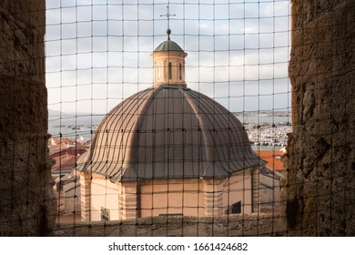 ALGHERO, SARDINIA, ITALY - SEPTEMBER 18th 2019 : View of santa Ana dome topped by a cross throw the fence of a window. The grey round roof stands out from the blue sky.