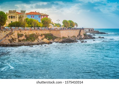 Alghero, Sardinia. Summer sunset view of the Alghero old town quarter with historic defense walls and the coastline of Gulf of Alghero at Mediterranean Sea