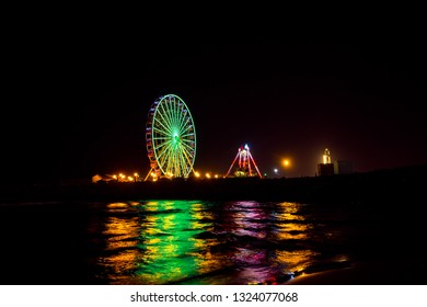 Algiers , Algeria - February 22, 2019 :  Ferris wheel in motion at amusement park at night at the sablette of algiers