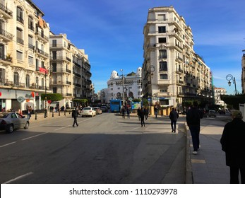 Algiers, Algeria - January 13, 2018: People are walking among French colonial architecture style in city center and Grande Poste D'Alger (Grand Post Office) up ahead.