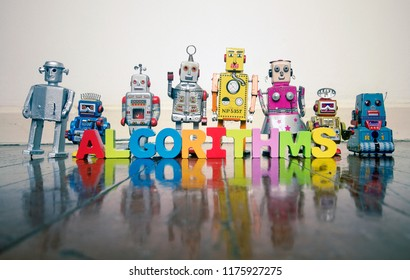 ALGORITHMS  wooden letters and retro robot toys on a wooden floor with reflection