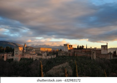 The Alhambra in Granada, over a hill and iluminate by golden light, on a cloudy sky