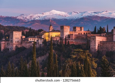 Alhambra historical monument at sunset with Sierra Nevada and its snowy mountains in the background and the Veleta peak. Photo taken from San Nicolas viewpoint in Granada, Andalusia, Spain
