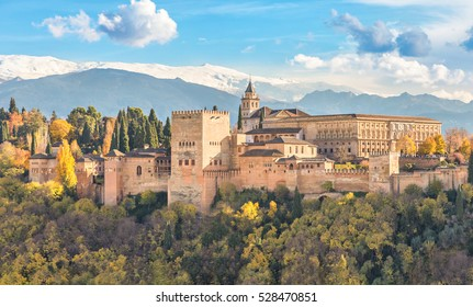 Alhambra - medieval Moorish fortress surrounded by yellow autumn trees with snow mountains on background, Granada, Andalusia, Spain