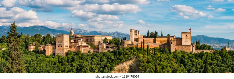 Alhambra panoramic scenic view with blue cloudy sky in Granada. Andalucia, Spain. High resolution image made by different photos stitched together.