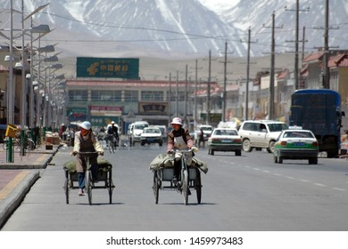 Ali (Shiquanhe), Tibet, China, Asia - April, 2005: Cityscape. Two women on cargo bikes on the main street of the city and Karakoram mountains on the background..