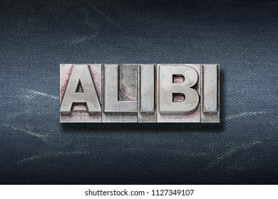 alibi word made from metallic letterpress on dark jeans background