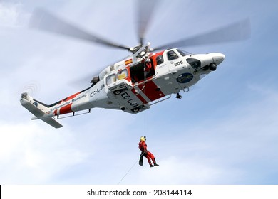 ALICANTE COAST, SPAIN - JULY 5: The helicopter of the Spanish  Maritime Rescue Team and his rescuers training over the deck of a coast guard ship, on july 5, 2014 in Alicante coast.