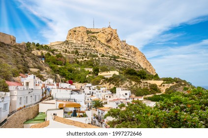 Alicante old town and Santa Barbara Castle on Benacantil hill. Narrow streets and white houses on hillside in ancient neighborhood El Barrio or Casco Antiguo Santa Cruz, Costa Blanca region in Spain.