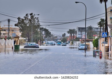 Dénia, Alicante, Spain 01/20/20 Storm Gloria floods the roads with sea water. Stranded cars and buses are abandoned in the deep water. Palm tree lined road. Parked cars filled with water.
