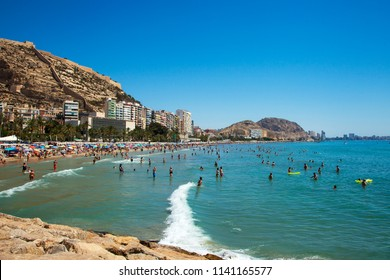Alicante, Spain, 09/07/2018: Tourists are resting on a city beach near the port of Alicante. Spanish beach. Holidays in Spain.