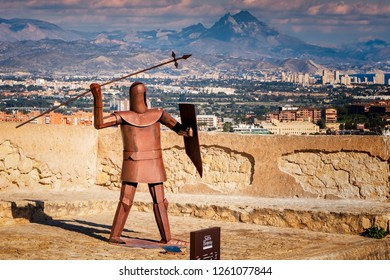 Alicante, Spain. Circa February 2017. View of metal sculpture of a warrior throwing a spear in Santa Barbara castle, with the city of Alicante, Spain, in the background.