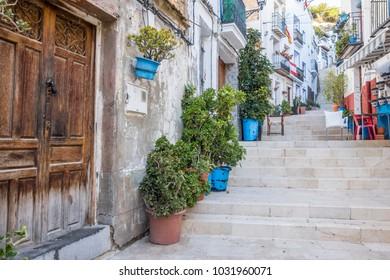 ALICANTE, SPAIN- JANUARY 18, 2018: Colored picturesque houses, street.Typical neighborhood historic center, casco antiguo,barrio santa cruz.Alicante, Spain.