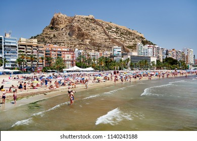 Alicante, Spain- June 26, 2018: Lot of people sunbathing, swimming on famous sandy Postiguet Beach in summer. Santa Barbara castle. Alicante is main tourist resort city in Costa Blanca. Europe Spain