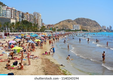 Alicante, Spain- June 26, 2018: Lot of people sunbathing, swimming on famous sandy Postiguet Beach in Alicante city at summer. Alicante is a main tourist resort city on the Costa Blanca. Europe Spain