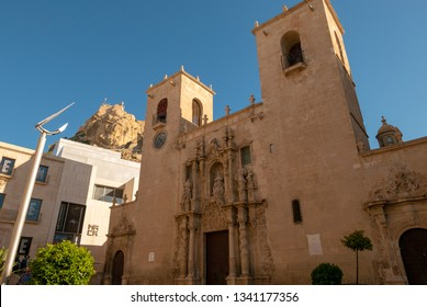 ALICANTE, SPAIN - MARCH 12, 2019: facade of the Alicante co-cathedral, in the background you can see the Santa Barbara castle