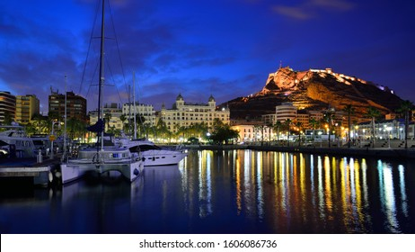 Alicante, Spain - May 15, 2019: Beautiful Alicante Marina night view with Santa Barbara Castle, yachts and reflections in the water.