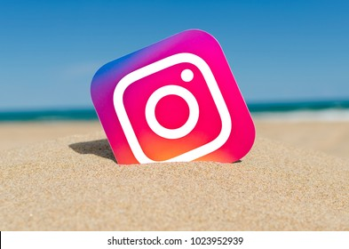 Alicante, Spain - September 15, 2016: Instagram logotype camera printed on paper and placed in the sand against the sea. Instagram - free application for sharing photos and videos.