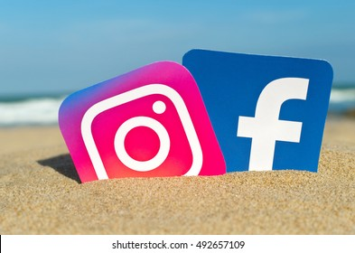 Alicante, Spain - September 15, 2016: Popular social media logos Instagram and Facebook printed on paper and placed in the sand against the sea.