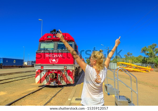 Alice Springs, Northern Territory, Australia - Aug 29, 2019: happy tourist woman with raised arms in front of The Ghan luxury passenger train at Alice Springs station. Tourism in Central Australia.