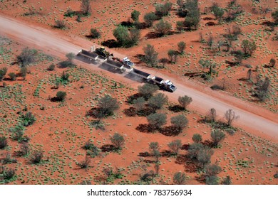 ALICE SPRINGS, NT, AUSTRALIA - NOVEMBER 21: Trucks with trailers and bulldozer for road works on unsealed road in outback area, on November 21, 2017 in Alice Springs, Australia