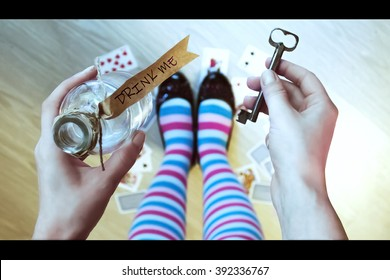 Alice in wonderland. Background. Key and potion in hands against a floor