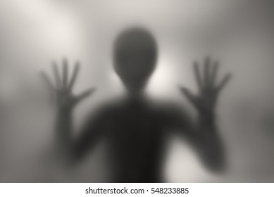 Alien behind a matte glass. Blurred image.