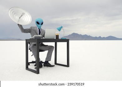 Alien businessman sitting at his office desk trying to communicate holding up a satellite dish