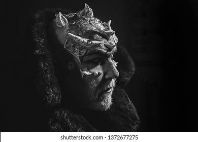 Alien, demon, sorcerer makeup. Horror and fantasy concept. Man with thorns or warts. Demon on black background, copy space. Senior man with white beard dressed like monster in darkness.