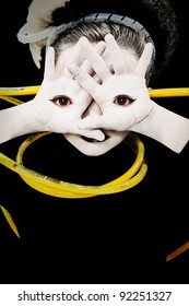 Alien girl child portrait with eyes on palms of hands and yellow tubes attached.