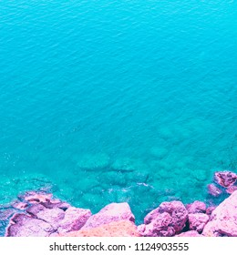 alien sea landscape with pink stones. bright neon colors. minimal and surreal. summer vacation.