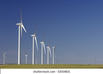 aligned group of modern windmills in a field