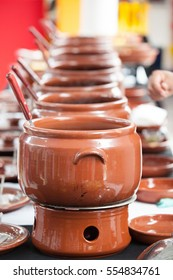 Aligned row of feijoada cookware on table