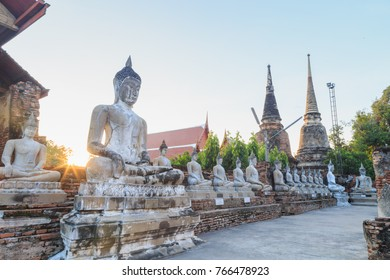 Aligned Sitting Buddha Statues with ancient ruin of temple at wat yai chaimongkol.The favorite historical attractions of Ayuttaya Thailand.