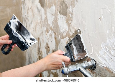 Aligning wall a painters putty, painter hands holding stainless steel spatulas, close-up.