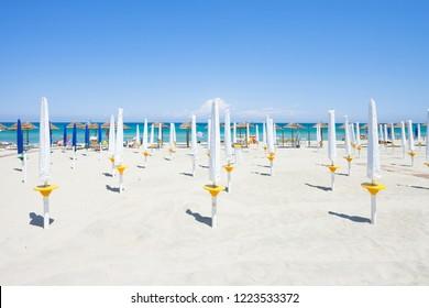Alimini Grande, Apulia, Italy - Folded sunshades at the beautiful beach of Alimini Grande