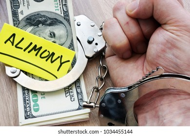 Alimony and hand in handcuffs. Legal separation.
