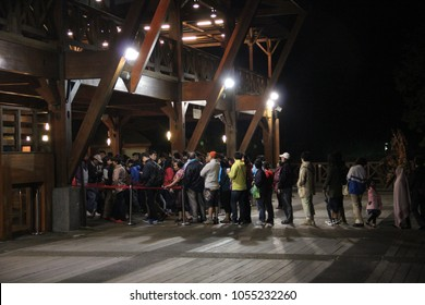 Alishan National Scenic Area,  Chiayi County, Taiwan - 26 Sept 2014: People lining up to get into the rain station at night