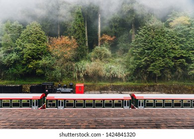 ALISHAN, TAIPEI. DEC 28, 2017: Red trains in Alishan Forest Railway stop on the platform of Zhaoping railway station with trees and fog in the background in Alishan, Taiwan.
