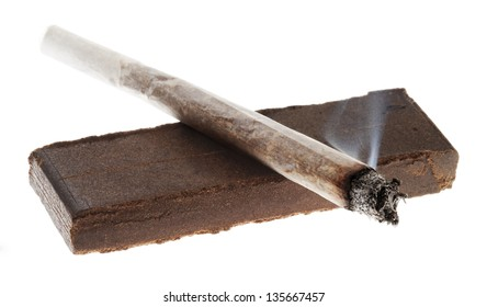 Alit joint laid on a 20 grams piece of Hashish, isolated on white background. This piece represents the shape and weight of a double retail unit.
