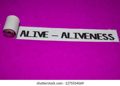 Alive - Aliveness text, Inspiration and positive vibes concept on purple torn paper