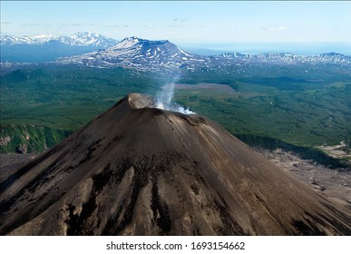 Alive smoking volcano in Kamchatka peninsula, Russia from helicopter. Mountain landscape of Kamchatka peninsula from above