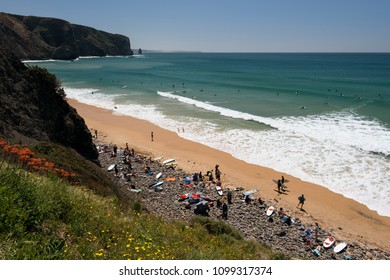 Aljezur, Portugal - April 27, 2018: Surfers gather at the  Arrifana Beach in Aljezur, Algarve, Portugal. The beach of Praia da Arrifana is inside the Vicentine Coast Natural Park,