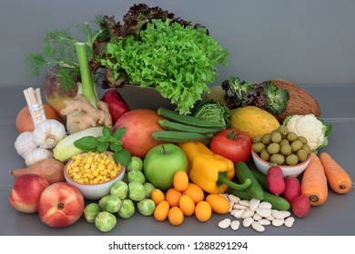 Alkaline health food of fresh vegetables, fruit, herbs, spice and dried legumes on grey wood table background. High in antioxidants, anthocyanins, fibre, minerals and vitamins.
