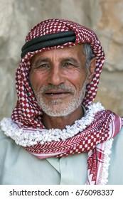 AL-KARAK, JORDAN - JUNE 09, 2014 : A portrait of a Bedouin man wearing traditional headwear. The headwear is a red and white checked pattern.