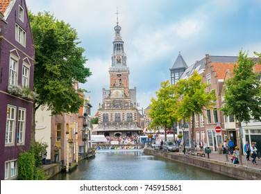 ALKMAAR, HOLLAND -AUGUST 18;  Historic ornately decorated Waag, or weigh house, surrounded by crowd people at end of canal lined by commercial and residential buildings August 18, 2017 Alkmaar Holland
