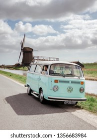 Alkmaar Netherlands April 2019, classic old vintage car van parked by historical windmill in Holland, Classic Minty Green and white VW Camper Van parked at countryside